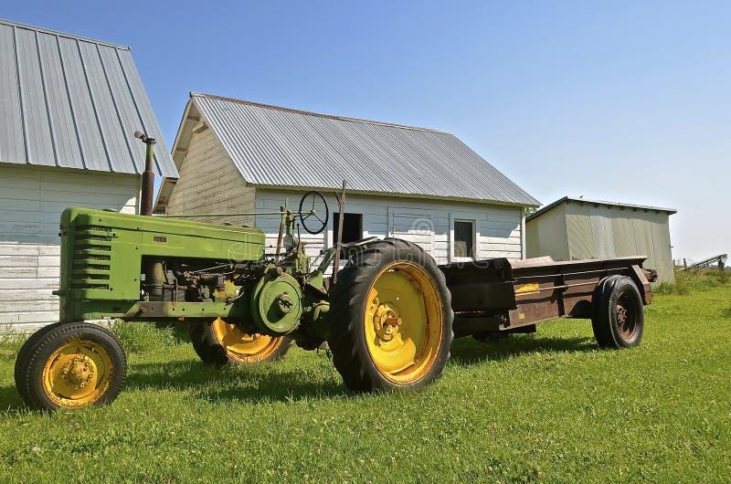 Tractor viejo que tira de un esparcidor de abono oxidado fotos de archivo