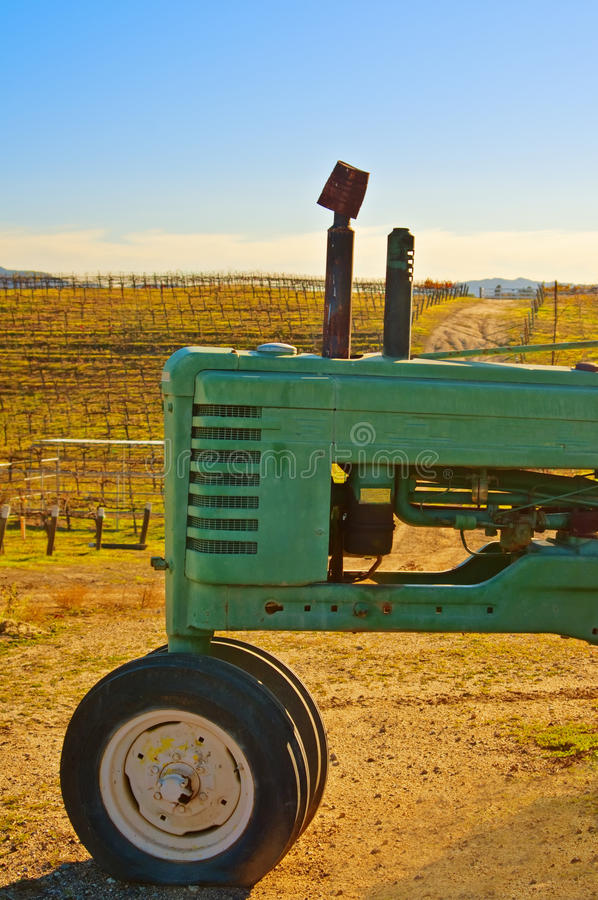 Tractor at the Vineyard. A bright green tractor on a vineyard hillside with grape vines in the background in the wine country and popular tourist destination of royalty free stock images