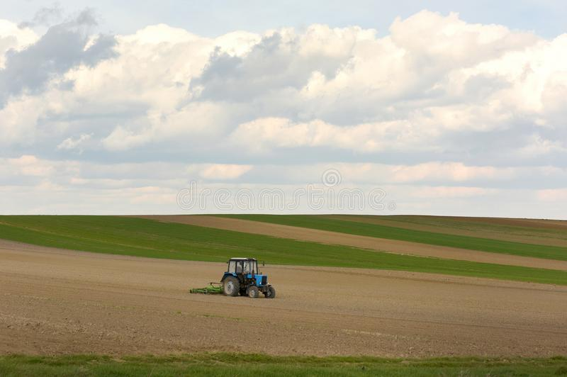 Tractor at work cultivating a field in spring, farmland, plowed royalty free stock images