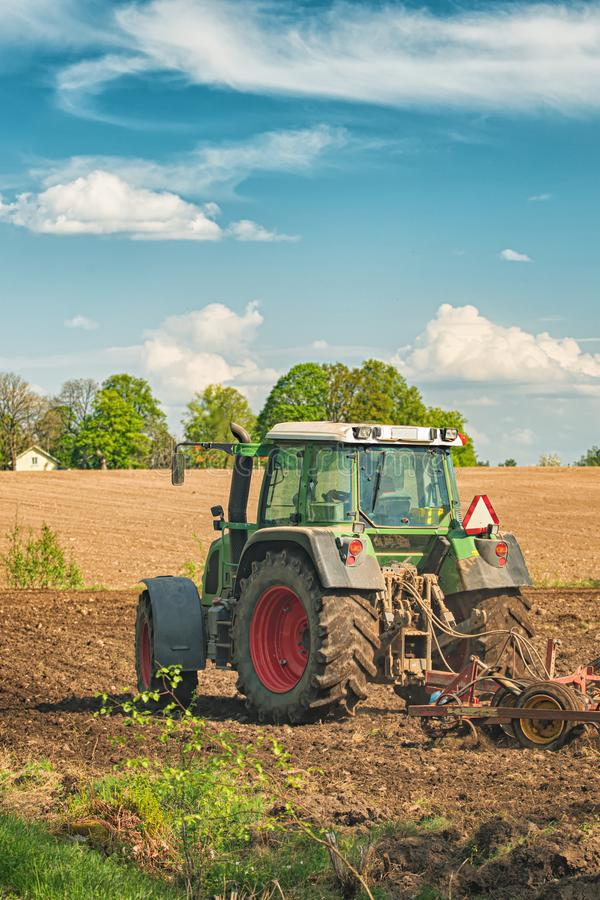 Tractor working on the farm, a modern agricultural transport, a farmer working in the field, fertile land, tractor on a sunset royalty free stock images