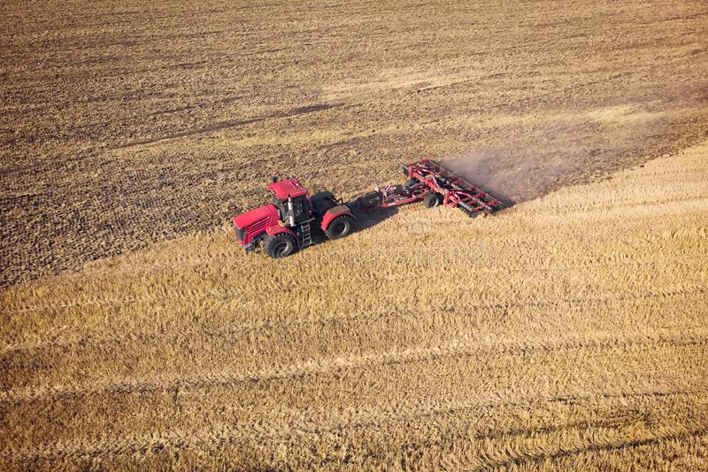 Tractor Working in the Fields, Aerial View. Hay on the field. The view from the top. Tractor harvests dry grass.  stock photo