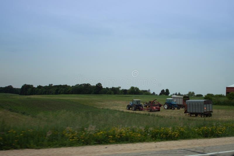 Tractor y camiones en un campo imagen de archivo libre de regalías