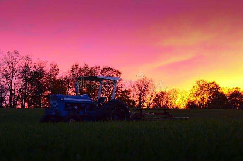 Tractor y hilera de árboles en la puesta del sol contra el cielo fotos de archivo
