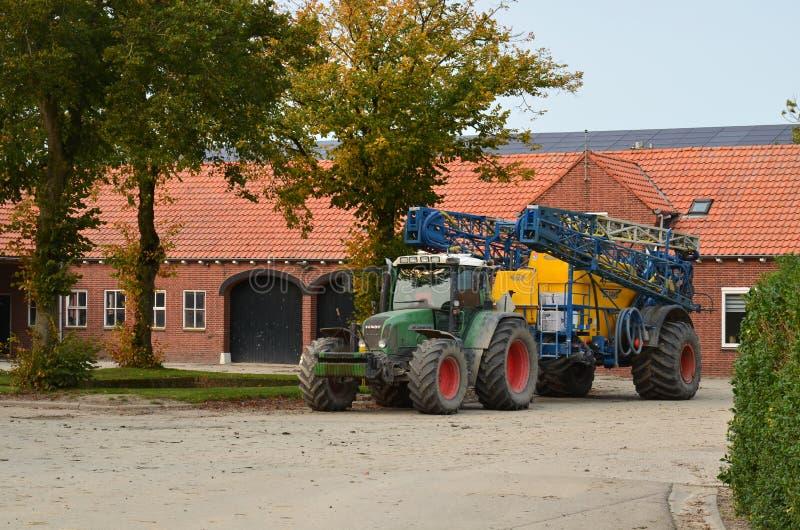 Tractor y rociador con doblar-en los auges del espray foto de archivo