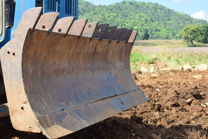 Tractores que preparan el suelo para plantar foco de /Selective imagen de archivo