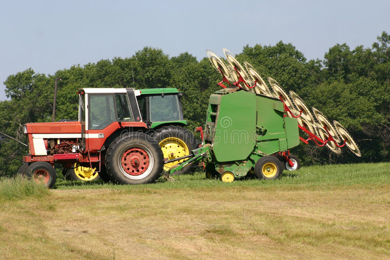 Tractors. Two field tractors with hay rakes and seeder stock photo