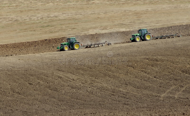 Tractors. Two tractors are cultivating field royalty free stock images