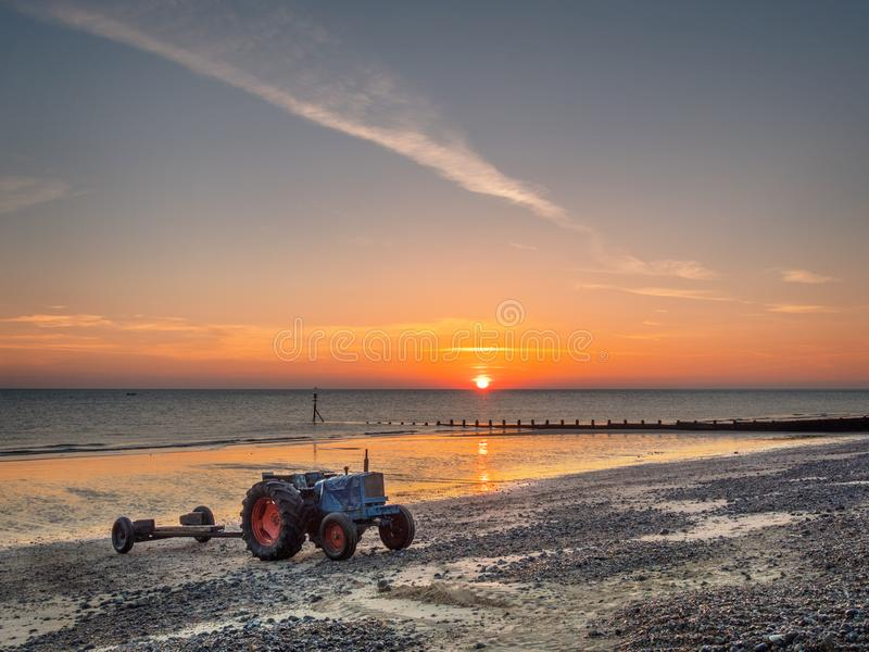 Tractors on Cromer Beach. Image of the beach and fishing boat tractors at sunrise Norfolk stock image