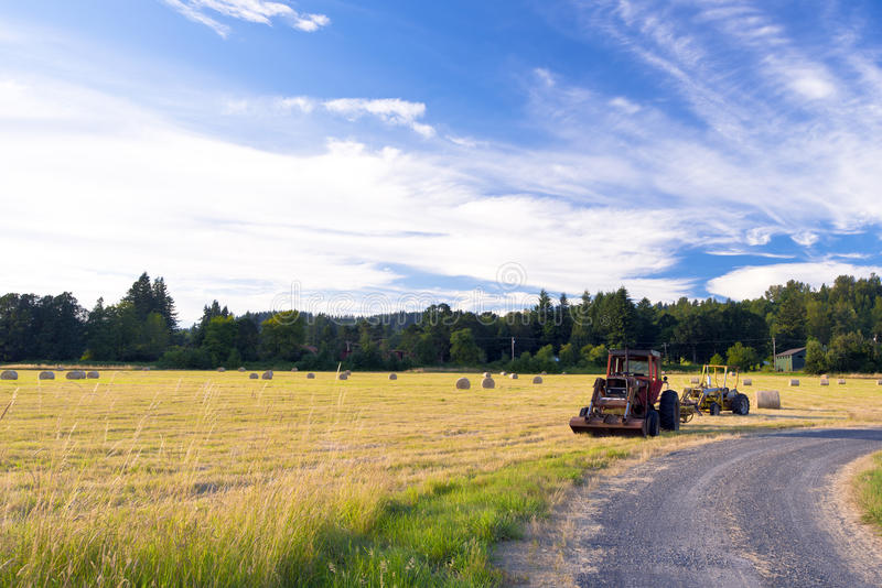Tractors on the field during the haymaking. Two tractors at the edge of the field and a country earth road after work cutting grass, which the tractor rolled royalty free stock photography