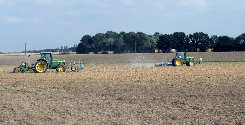 Tractors in the fields. Two tractors in the fields at work in the summer royalty free stock photos