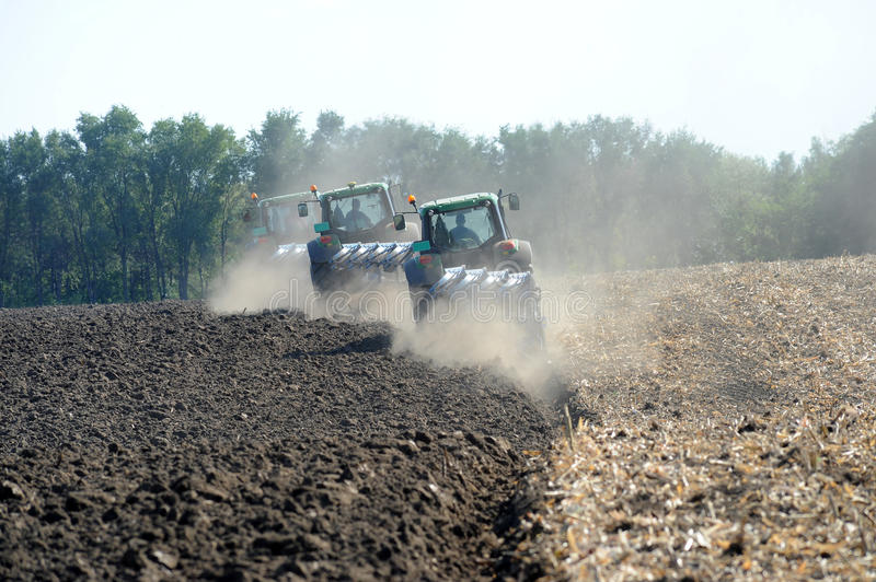 Tractors plowing royalty free stock photos