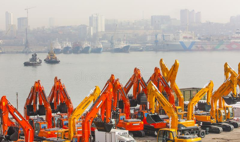 Tractors waiting loading and cranes in seaport of Vladivostok stock photography