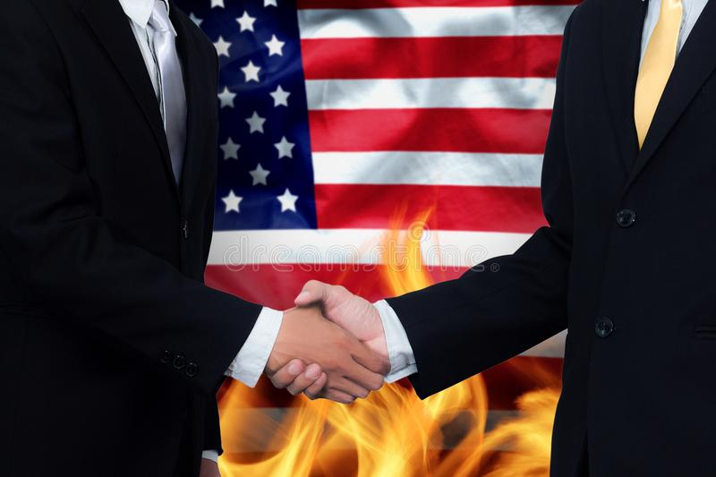 Trade agreements and business practices in the United States. Concept. hand of businessman shaking on America flag background and fire royalty free stock photo