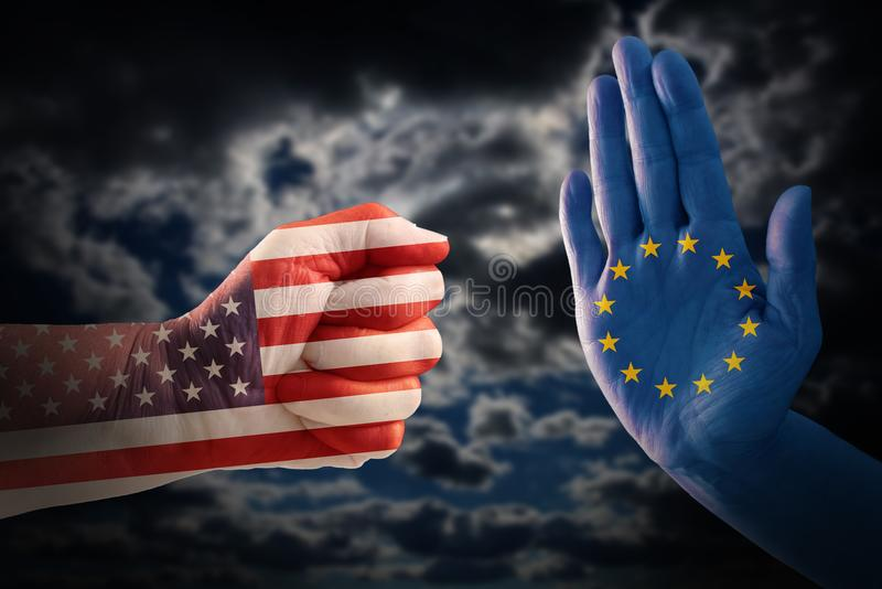 Trade conflict, fist with USA flag against a hand with European. Flag, dramatic cloudy sky in the background, political concept royalty free stock photo