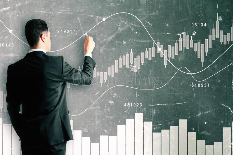 Trade and seminar concept. Businessman in suit drawing forex chart on chalkboard wall. Trade and seminar concept stock illustration