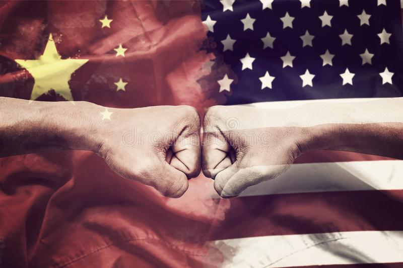 Trade war between USA and China concept. two clenched fists punch each other on USA and China flag background stock image
