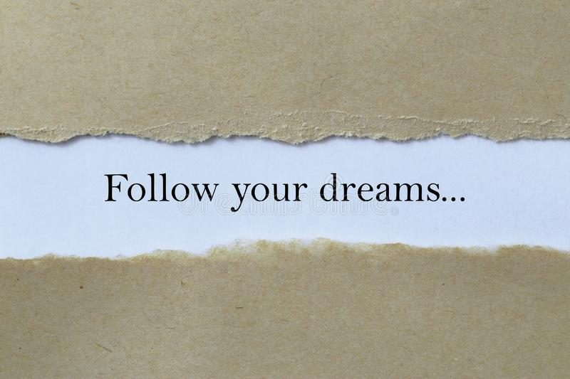 Follow your dreams heading. Behind ripped paper royalty free stock images