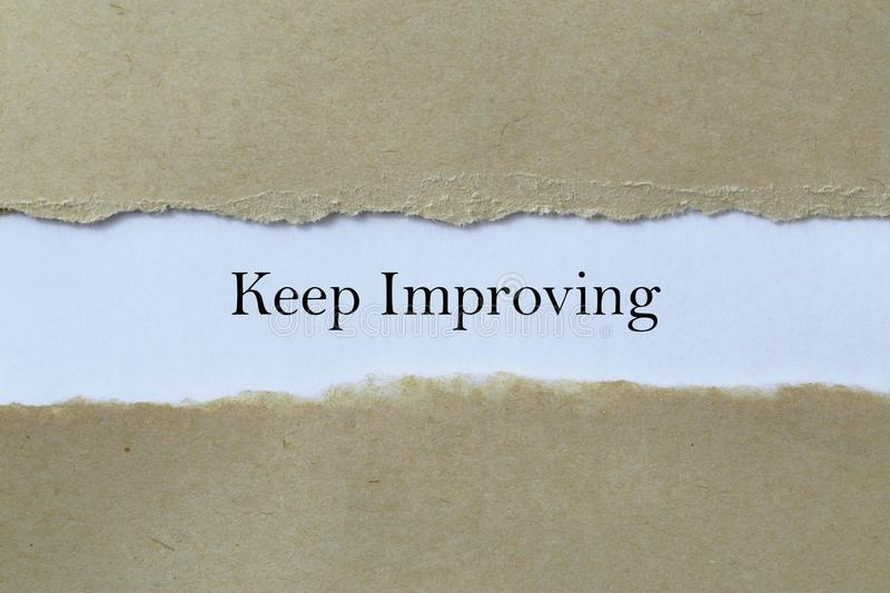Keep Improving. A torn brown paper revealing the words Keep Improving stock photos