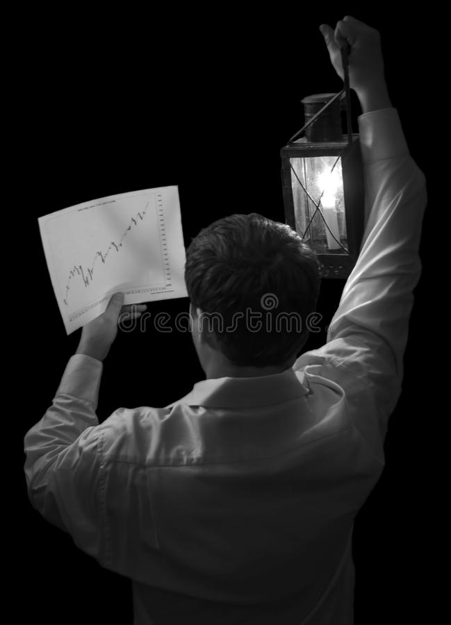 Trader looking for secret quotes. Black and white rear view of secretive stock market trader using lantern and night to look at graph of rising share prices royalty free stock images