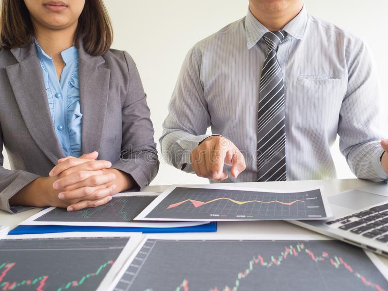 Trader team discussion and analyze stock graph report, set targets for online trading management success.  royalty free stock image