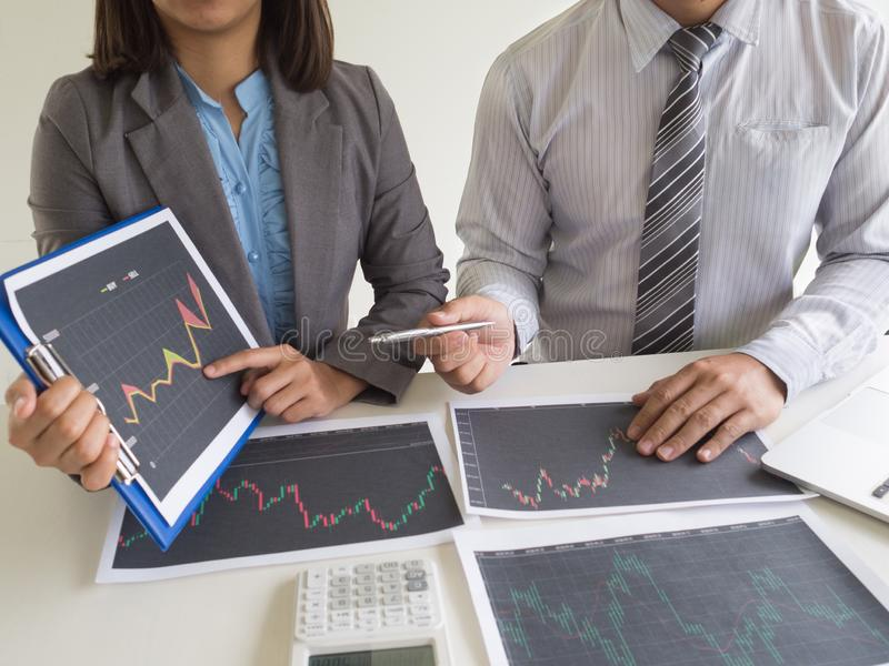 Trader team discussion and analyze stock graph report, set targets for online trading management success.  stock photos
