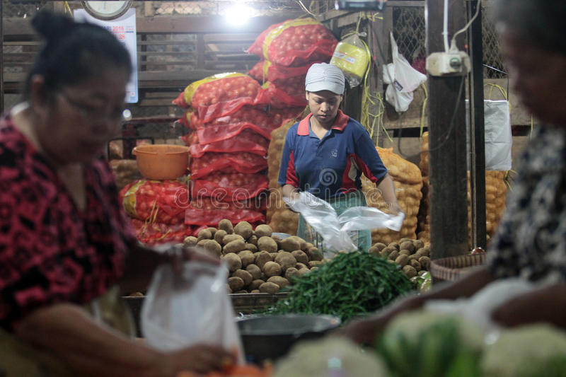 Traders arrange merchandise in the form of vegetable stock image