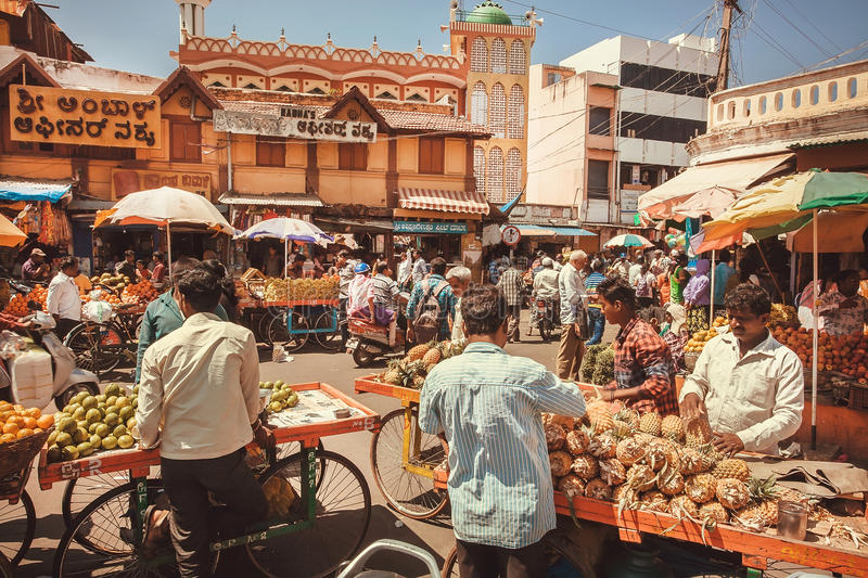 Traders of pineapples and tropical fruits talking with customers at street market stock photo