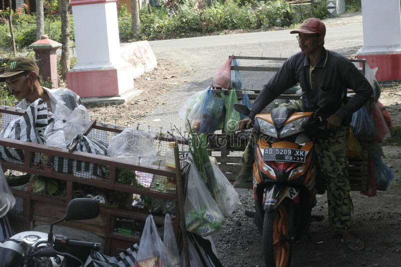 TRADERS VEGETABLES USING MOTORCYCLE TOUR. Vegetable traders wandering over the countryside using modern motorcycle Puhgogor serve buyers in the village royalty free stock photo