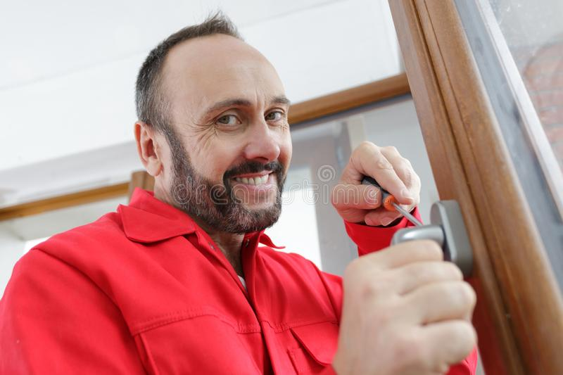 Tradesman adjusting window handle with screwdriver. Window royalty free stock images