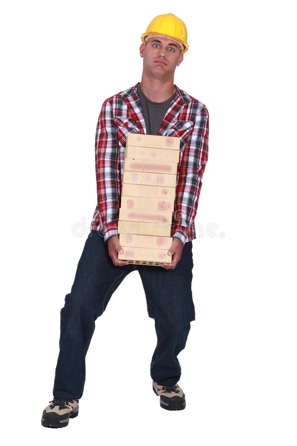 Tradesman carrying a heavy bricks royalty free stock photography
