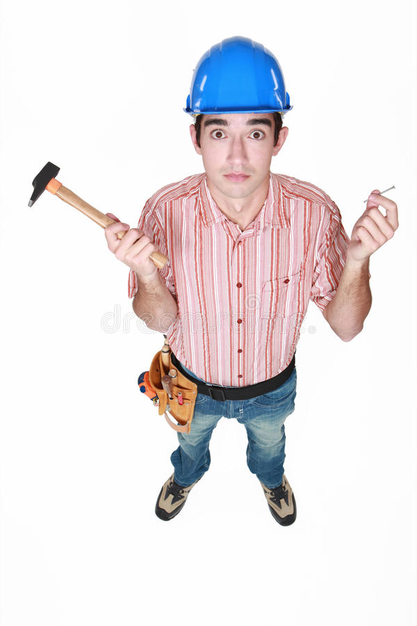 Tradesman holding a hammer. And a nail stock image