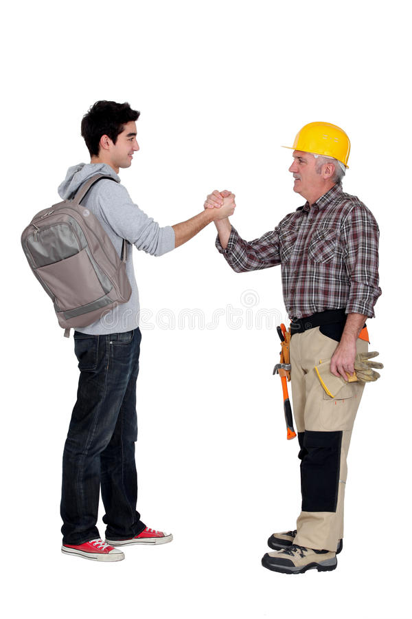 Tradesmen making a pact. Tradesman making a pact with a young man stock photos