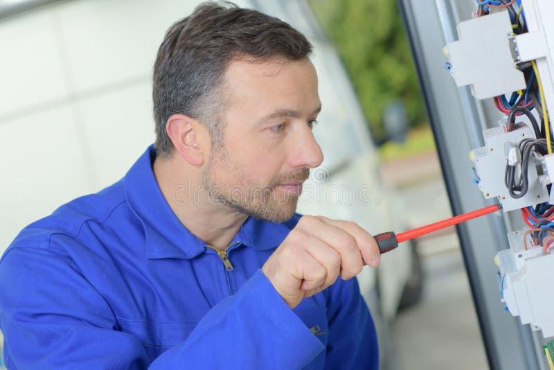 Tradesman repairing distribution board stock photography