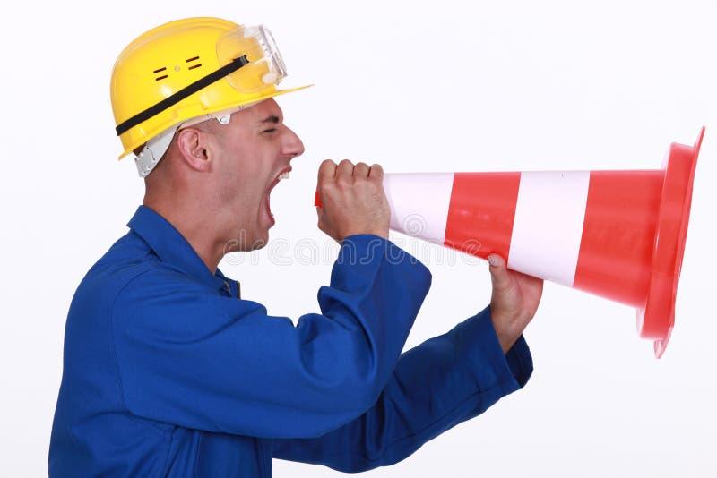 Tradesman screaming into a pylon stock photography