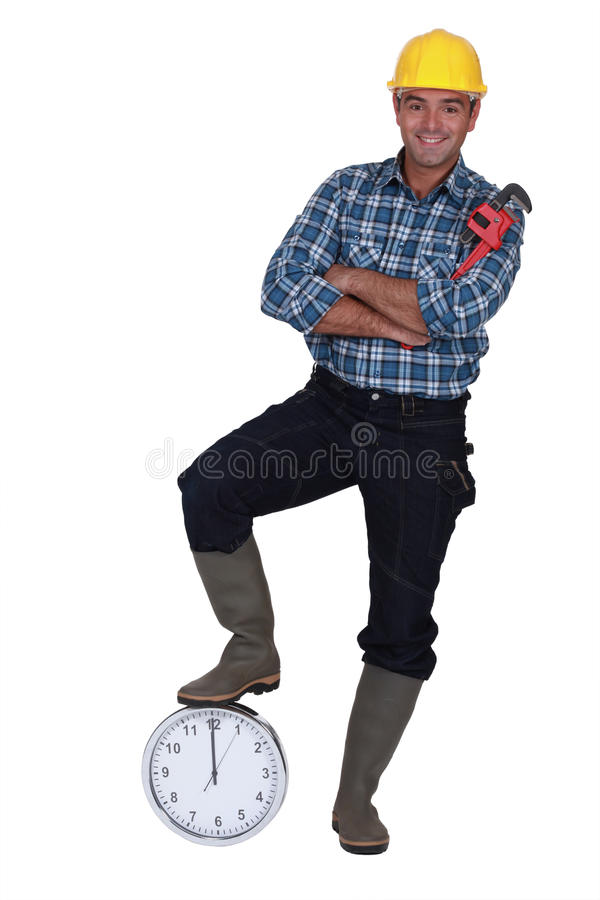Tradesman stood by a clock stock photography
