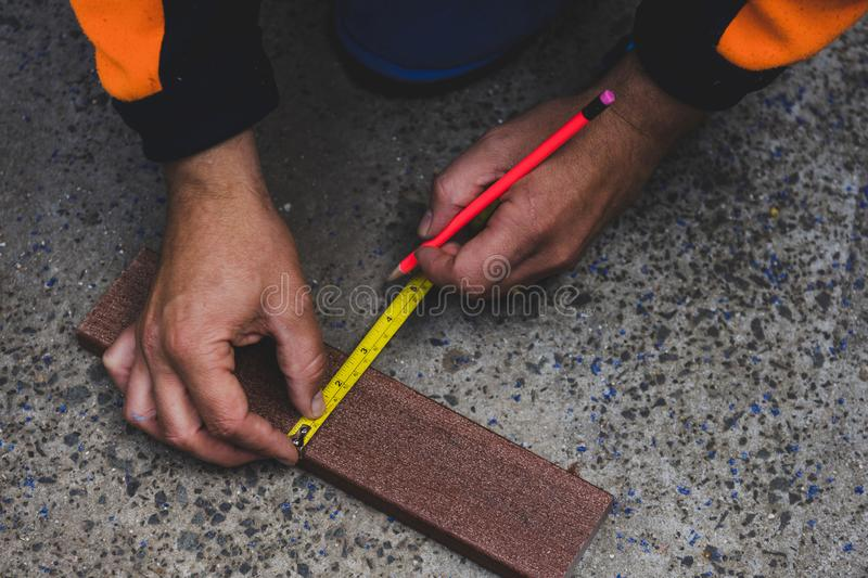 Tradesman taking measures and preparing timber to be cut to build a fence. Concept of do it yourself constructions stock photo