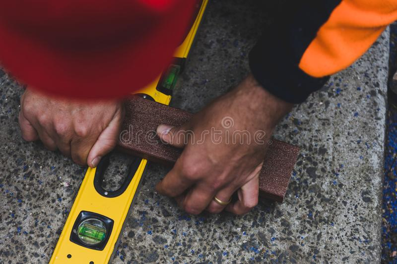 Tradesman taking measures and preparing timber to be cut to build a fence. Concept of do it yourself constructions stock photography