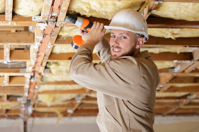 Tradesman używa świder na drewniany struktury stropować zdjęcie royalty free