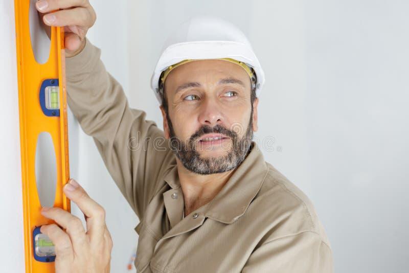 Tradesman u?ywa spirytusowego poziom na ?cianie zdjęcie stock