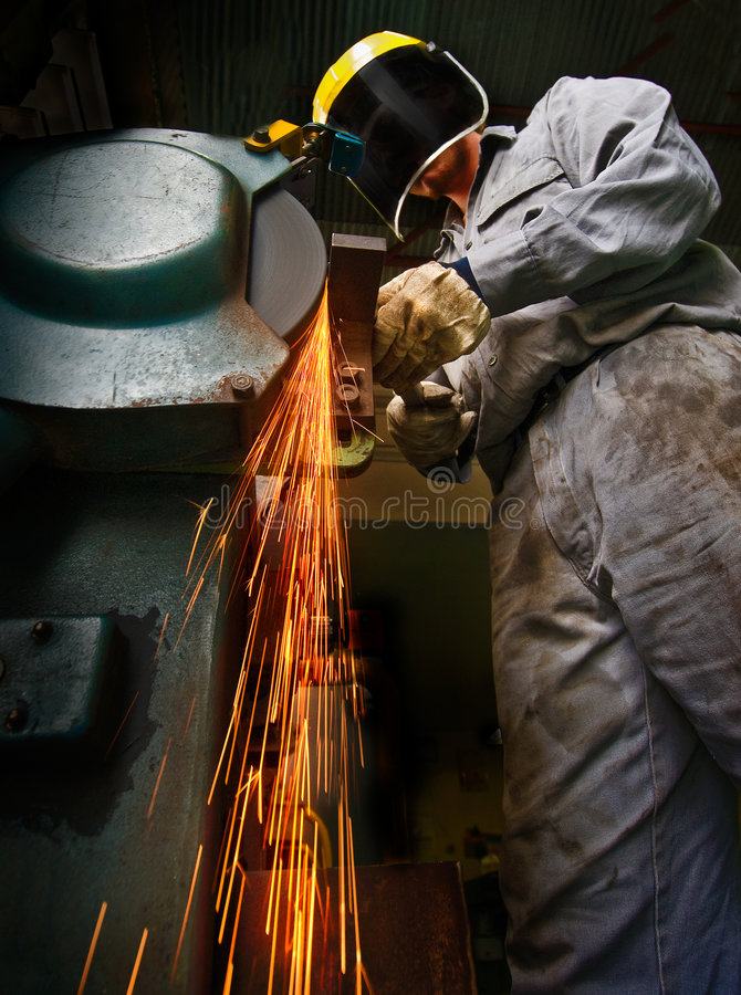 Tradesman at work grinding steel. stock photography