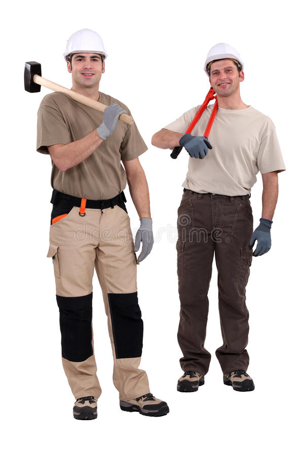 Tradesmen holding their tools. Over their shoulders stock photography