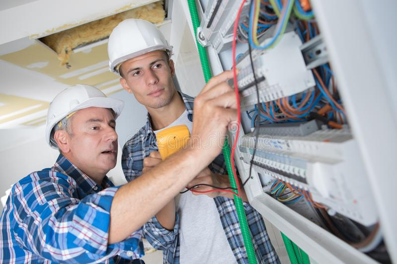 Tradesmen installing distribution board. Tradesmen installing a distribution board royalty free stock photos