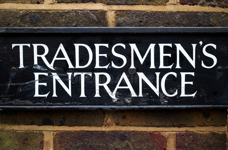 Tradesmen's Entrance Sign. Tradesman's Entrance sign on the exterior brick wall of a building. Once common in British society and ridiculed as part of the class royalty free stock image