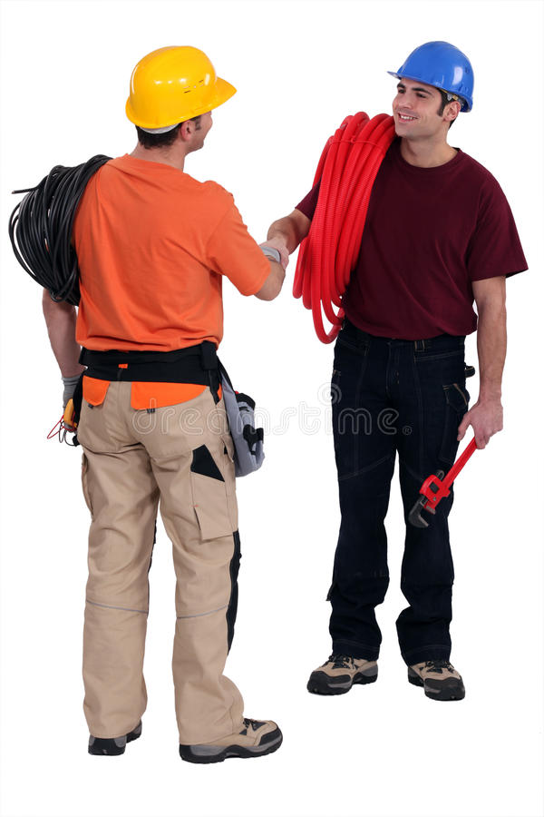 Tradesmen shaking hands. In agreement royalty free stock photography
