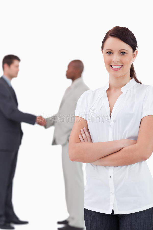 Tradeswoman with arms folded and hand shaking trading partners b. Ehind her against a white background stock photography