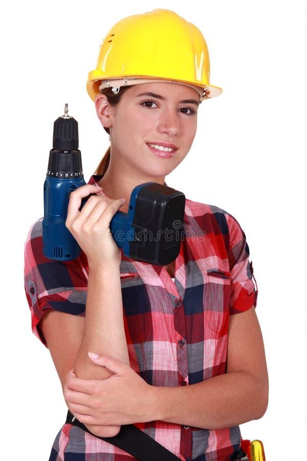 Tradeswoman che tiene un attrezzo a motore immagini stock