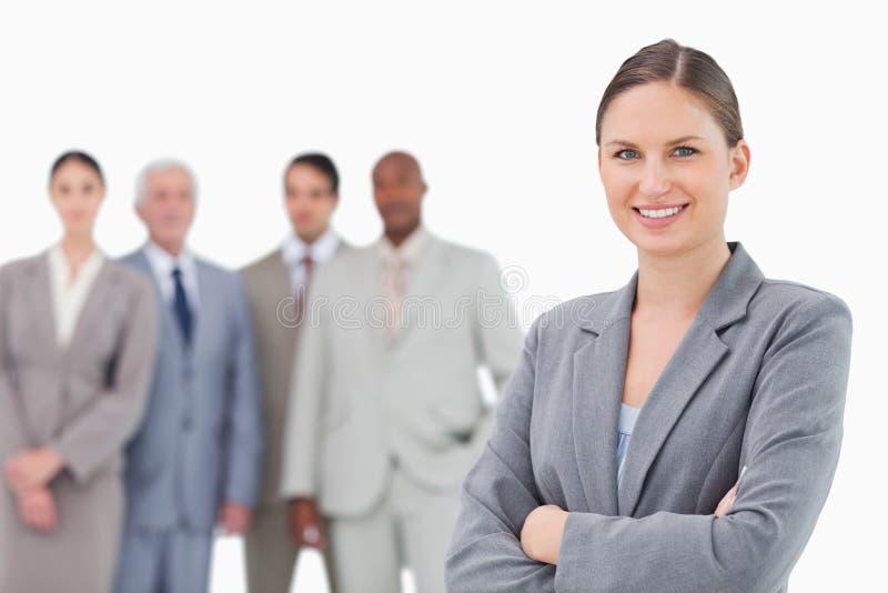 Tradeswoman de sourire avec des bras pliés et collègues derrière elle photographie stock