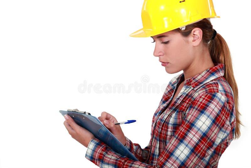 Tradeswoman filling in paperwork stock photos