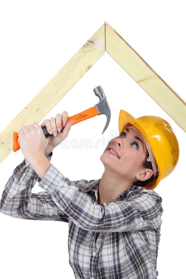 Tradeswoman hammering a frame royalty free stock photography