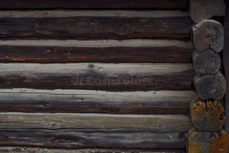 Tradições da construção de casa de madeira Textura da parede dos logs Fundo escuro foto de stock